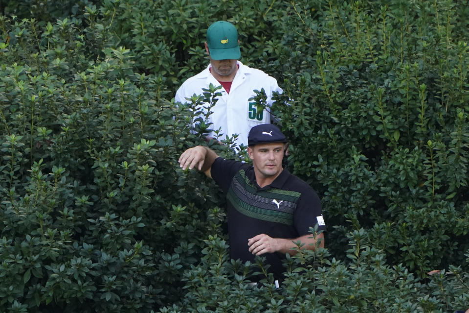 Bryson DeChambeau comes out of the bushes after looking for his ball on the 13th hole during the first round of the Masters golf tournament Thursday, Nov. 12, 2020, in Augusta, Ga. (AP Photo/Chris Carlson)