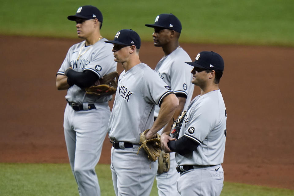 New York Yankees infielders, from left, third baseman Miguel Andujar, shortstop Gio Urshela, second baseman DJ LeMahieu, and first baseman Mike Ford, look on as pitcher Michael King warms up against the Tampa Bay Rays during the fifth inning of a baseball game Thursday, May 13, 2021, in St. Petersburg, Fla. (AP Photo/Chris O'Meara)