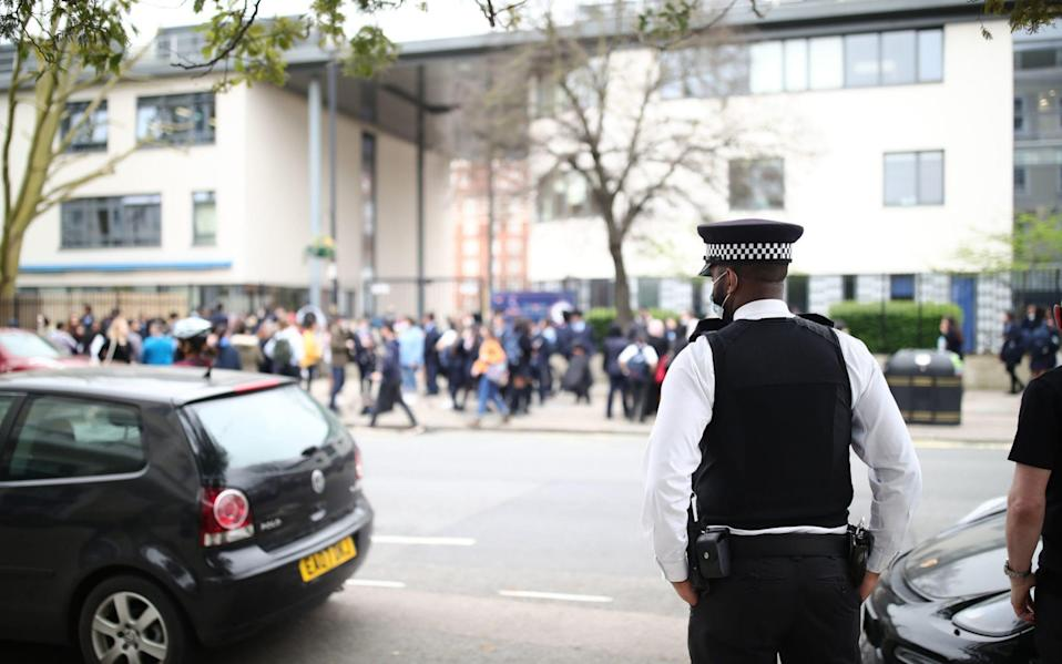 A police officer outside Pimlico Academy School, west London, where students have staged a walkout in protest over a school uniform policy that they claim is discriminatory and racist - Aaron Chown