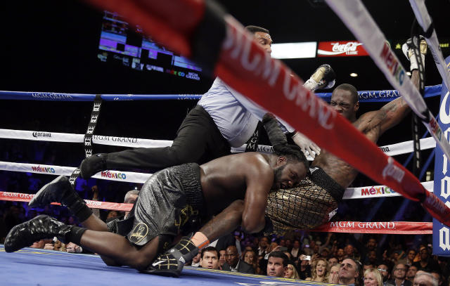 Referee Tony Weeks, left, Deontay Wilder, right, and Bermane Stiverne fall to the mat during the WBC heavyweight championship boxing match Saturday, Jan. 17, 2015, in Las Vegas. (AP Photo/Isaac Brekken)