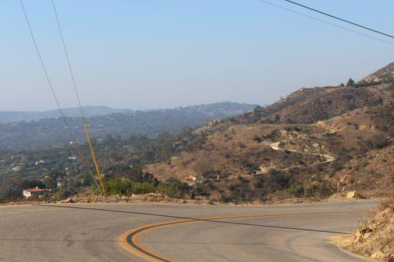 Hazy-smoke skies, with wooded Montecito on left and a cleared out high road driveway on right.
