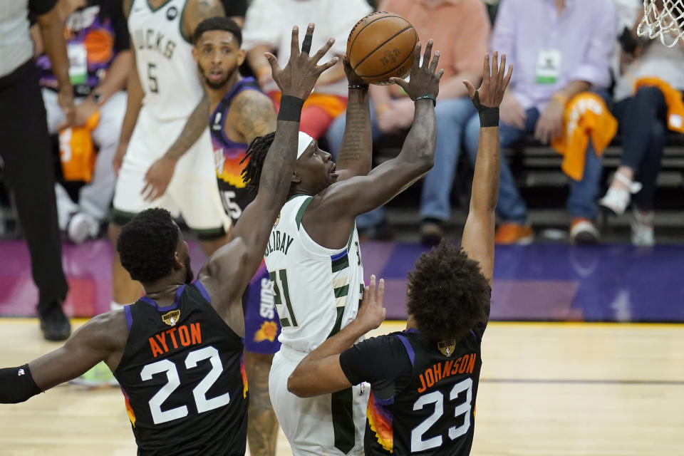 Milwaukee Bucks guard Jrue Holiday, middle, shoots against Phoenix Suns center Deandre Ayton (22) and forward Cameron Johnson (23) during the first half of Game 5 of basketball's NBA Finals, Saturday, July 17, 2021, in Phoenix. (AP Photo/Ross D. Franklin)