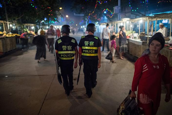 Police patrol in a night market near the Id Kah Mosque in Kashgar in China's Xinjiang Uighur Autonomous Region, a day before the Eid al-Fitr holiday on June 25, 2017.