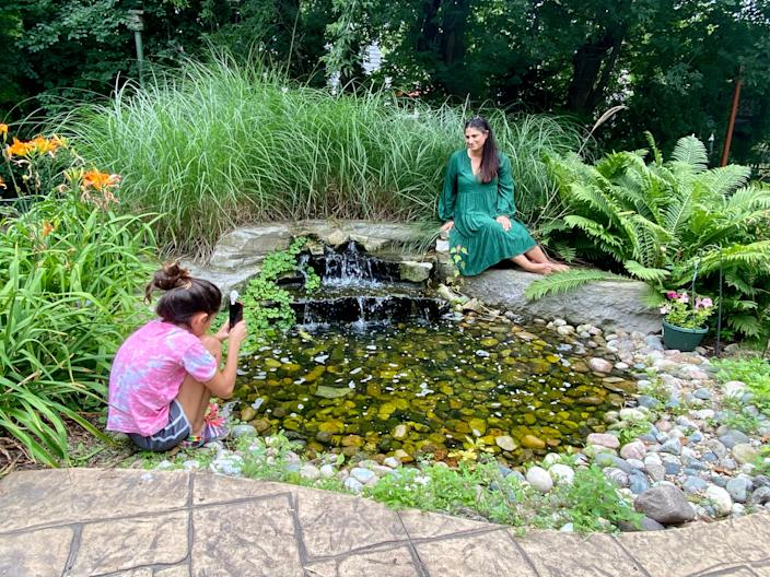 Dr. Mona Hanna-Attisha poses as her daughter, Layla, takes her picture in the backyard of their home in Michigan.
