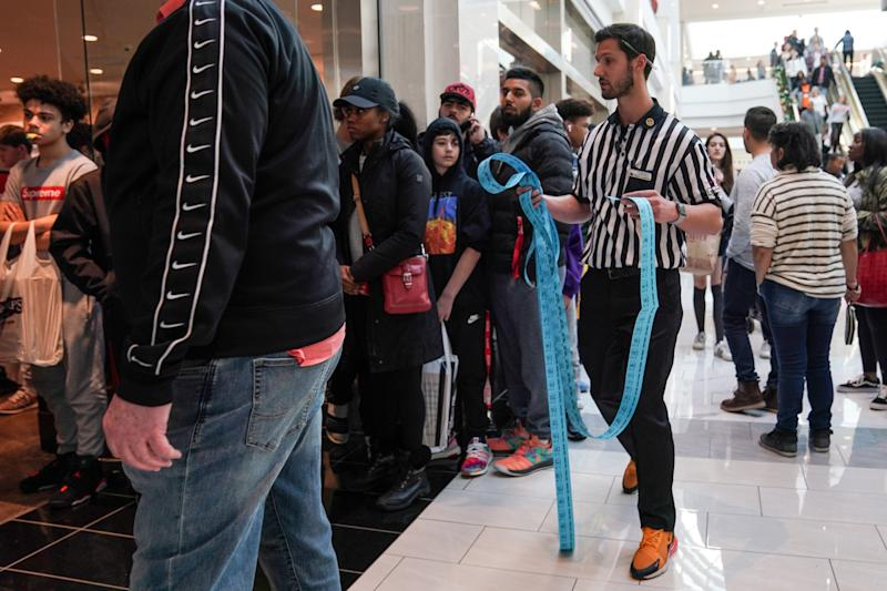 A Foot Locker employee hands out tickets to a line of people waiting for Kanye West's Yeezy shoes in King of Prussia mall on Black Friday, a day that kicks off the holiday shopping season, in King of Prussia, Pennsylvania, U.S., on November 29, 2019. REUTERS/Sarah Silbiger
