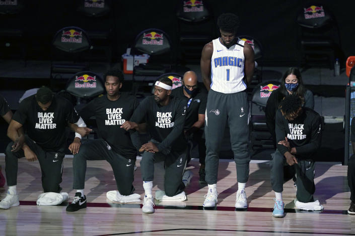 Magic forward Jonathan Isaac stands as others kneel before the start of a game between Brooklyn and Orlando. (Ashley Landis - Pool/Getty Images)