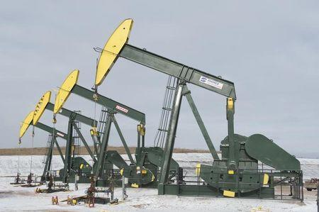 Pumpjacks taken out of production temporarily stand idle at a Hess site while new wells are fracked near Williston