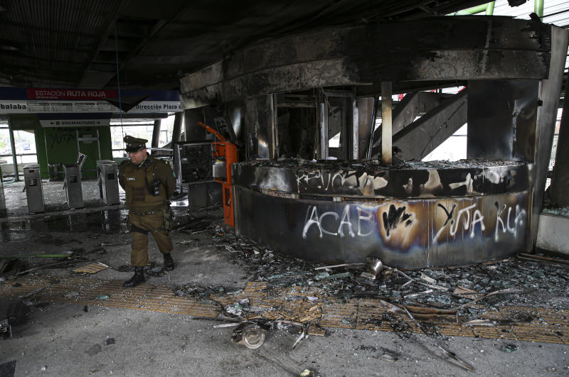 A police officer walks in a subway station that was torched during last night's protests, in Santiago, Chile, Saturday, Oct. 19, 2019. The protests started on Friday afternoon when high school students flooded subway stations, jumping turnstiles, dodging fares and vandalizing stations as part of protests against a fare hike, but by nightfall had extended throughout Santiago with students setting up barricades and fires at the entrances to subway stations, forcing President Sebastian Pinera to announce a state of emergency and deploy the armed forces into the streets. (Photo: Esteban Felix/AP)