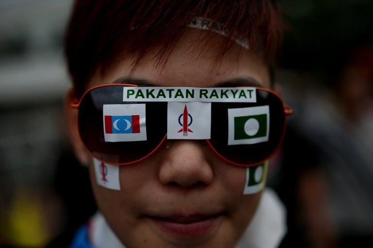 A young Malaysian opposition supporter displays the party's logo on her sunglasses as supporters gather at a stadium in Kelana Jaya, Selangor on May 8, 2013. Thousands of Malaysians dressed in mourning black gathered Wednesday to denounce elections which they claim were stolen through fraud by the coalition that has ruled for 56 years