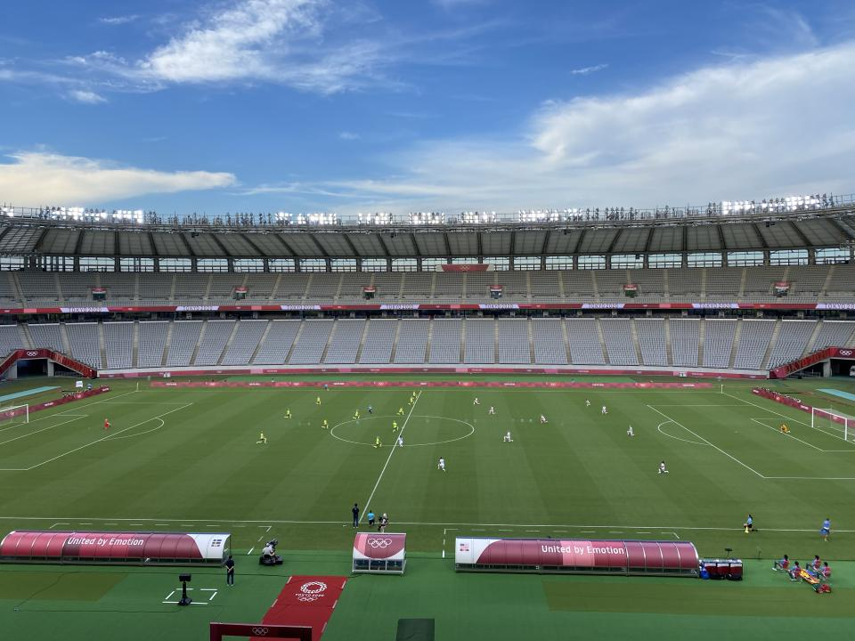 The USWNT and Sweden take a knee before their Olympic opener on Wednesday in Tokyo. (Henry Bushnell/Yahoo Sports)