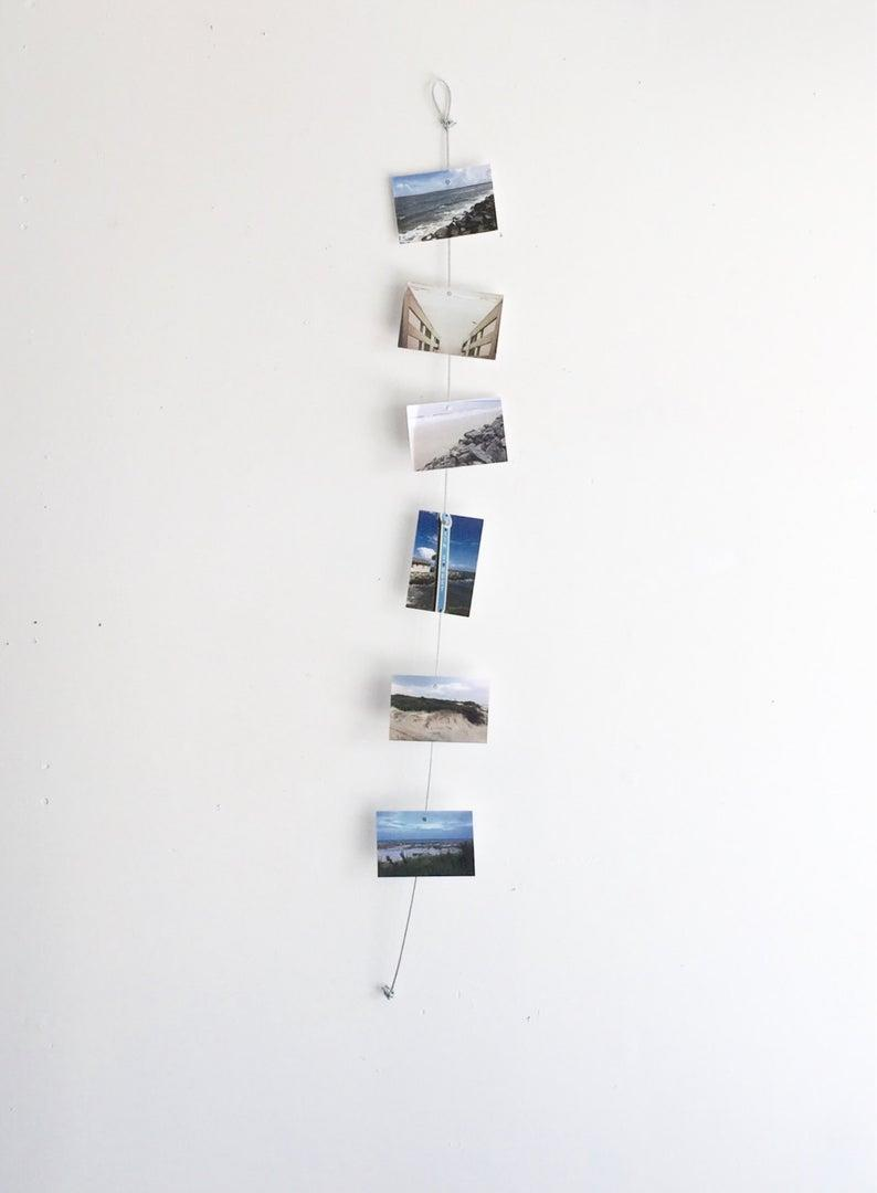 """<h3><a href=""""https://www.etsy.com/listing/203676955/downtown-vertical-cable-photo-holder"""" rel=""""nofollow noopener"""" target=""""_blank"""" data-ylk=""""slk:Etsy Vertical Cable Photo Holder"""" class=""""link rapid-noclick-resp"""">Etsy Vertical Cable Photo Holder</a> </h3><br><br>Minimize holes in the wall while still getting your memories off the ground with this bestselling, vertical picture-hanging wire.<br><br><strong>LeeArtDesigns</strong> Vertical Cable Photo Holder, $, available at <a href=""""https://www.etsy.com/listing/203676955/downtown-vertical-cable-photo-holder"""" rel=""""nofollow noopener"""" target=""""_blank"""" data-ylk=""""slk:Etsy"""" class=""""link rapid-noclick-resp"""">Etsy</a>"""