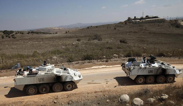 UNDOF armoured personnel carriers escort a convoy of vehicles leaving the Syrian side of the Golan Heights on September 15, 2014 (AFP Photo/Jalaa Marey)