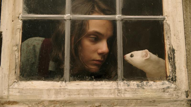 Lyra (Dafne Keene) with her daemon Pantalaimon, seen here as an ermine. (BBC/© Bad Wolf/HBO)