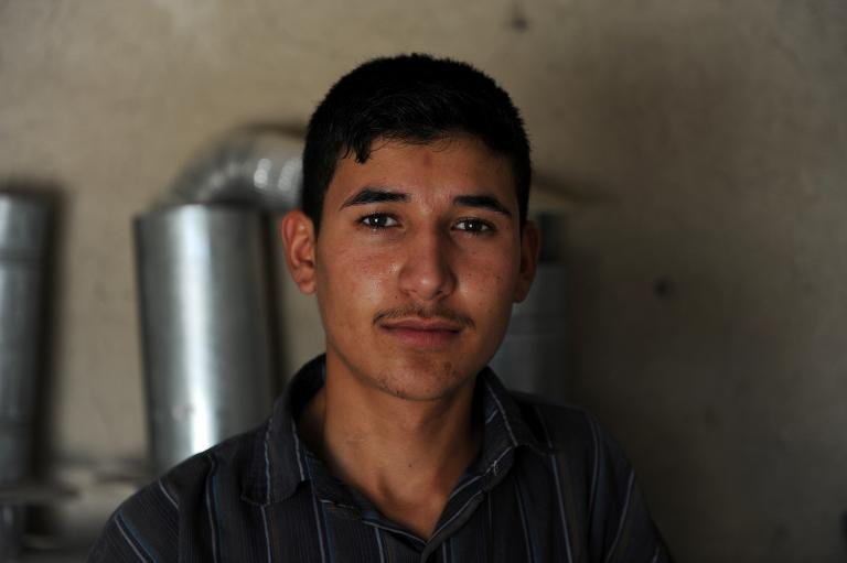 Unemployed Afghan Saber Rezayee is pictured at his family's heater shop in Mazar-i-Sharif on September 20, 2013