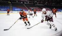 Anaheim Ducks defenseman Jacob Larsson, left, pursues the puck with Colorado Avalanche left wing Kiefer Sherwood in the first period of an NHL hockey game Friday, March 5, 2021, in Denver. (AP Photo/David Zalubowski)