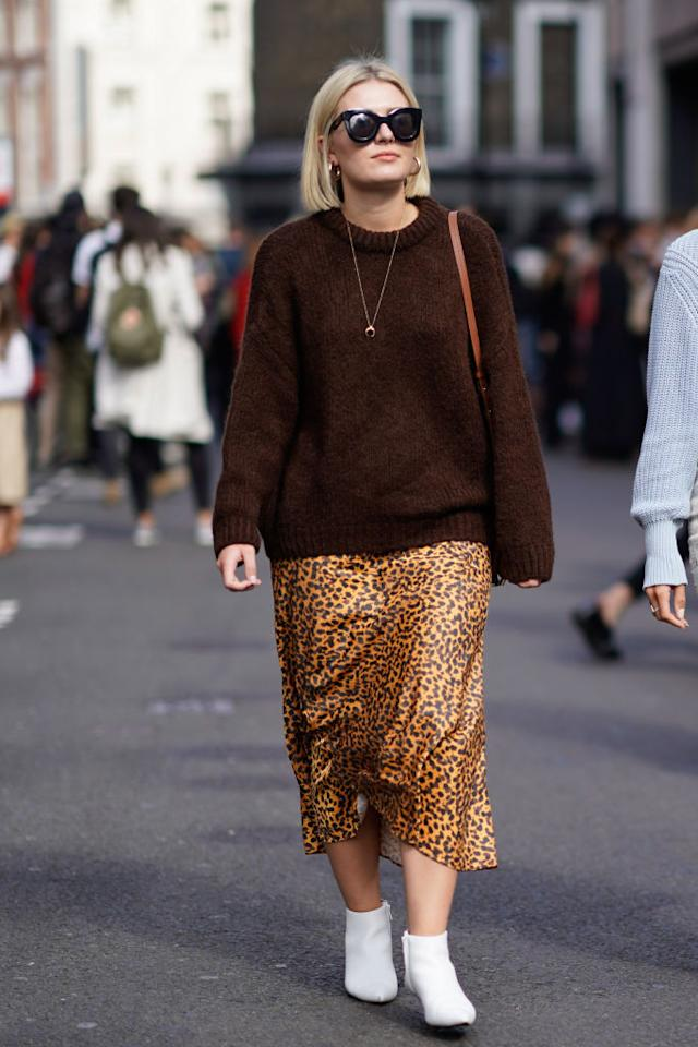 <p>A London Fashion Week guest wears a brown pullover, leopard-print skirt, and white boots on Sept. 15, 2018, in London. (Photo: Edward Berthelot/Getty Images) </p>