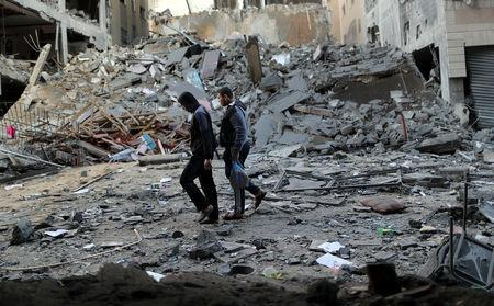 Palestinians walk past the remains of a building that was destroyed by Israeli air strikes, in Gaza City November 13, 2018. REUTERS/Suhaib Salem