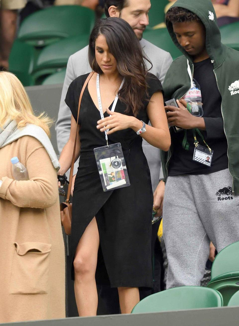 <p>For the Wimbledon Tennis Championships in London, Markle wears a black wrap dress.</p>