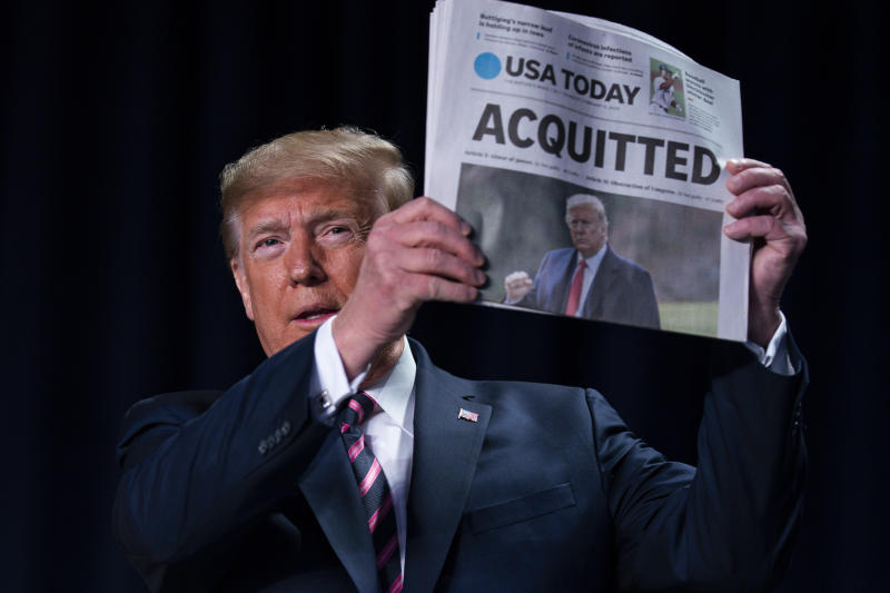 """President Trump holds up a newspaper with the headline that reads """"ACQUITTED"""" during the 68th annual National Prayer Breakfast at the Washington Hilton on Thursday. (AP Photo/ Evan Vucci)"""