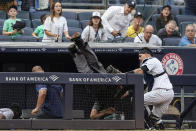 New York Yankees catcher Gary Sanchez, right, watches as home plate umpire Angel Hernandez, center, flips over the railing of the Tampa Bay Rays dugout during the sixth inning of a baseball game Sunday, Oct. 3, 2021, in New York. Gio Urshela caught a foul ball by Austin Meadows for an out on the play. (AP Photo/Frank Franklin II)