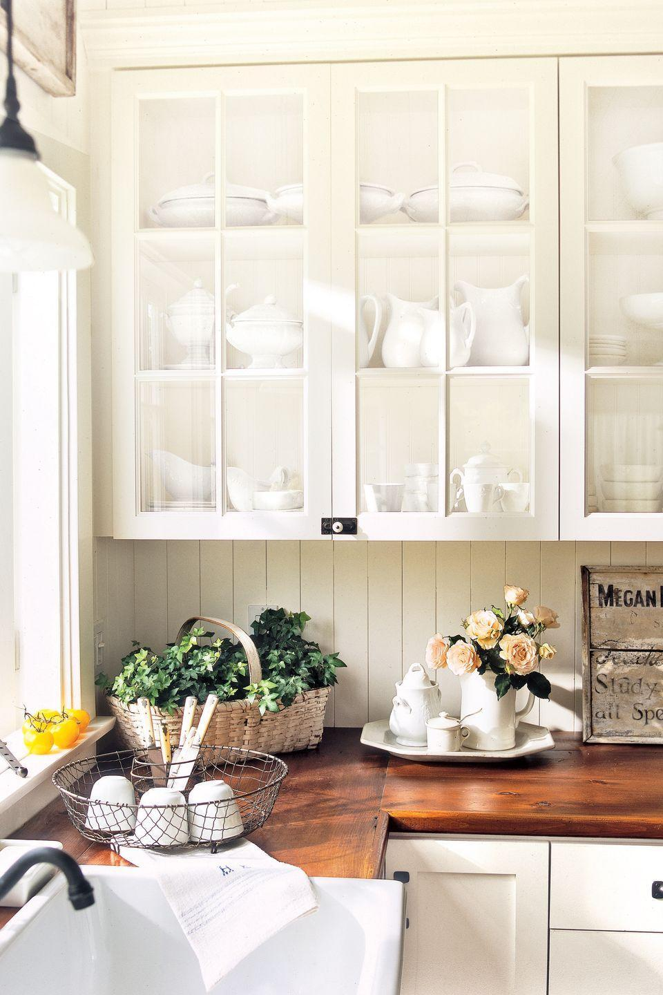 <p>White's inherent brightness makes an impact in an open-plan kitchen with high ceilings, providing additional light and opening up the space. The homeowner added cozy, unexpected old-house details—like kitchen countertops crafted from salvaged wood floors.</p>
