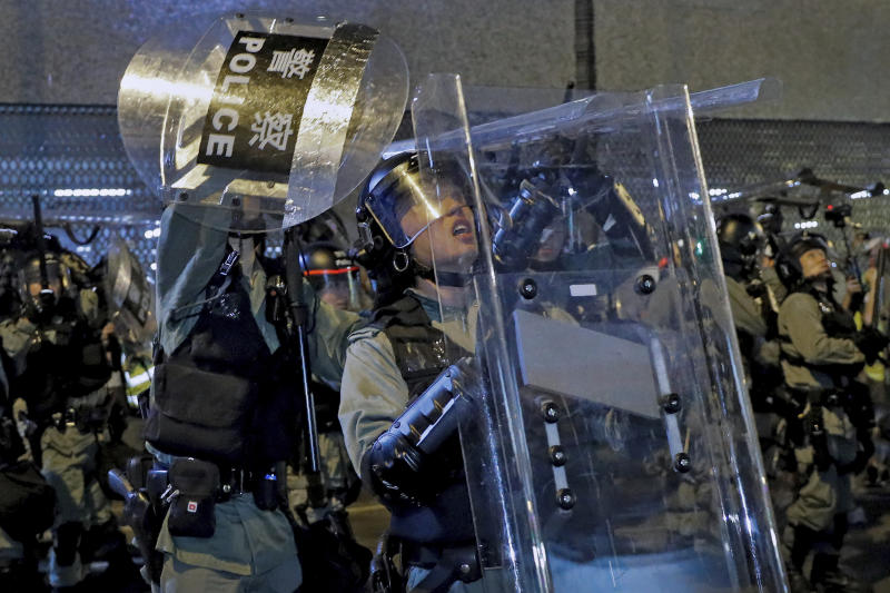 In this Sunday, July 14, 2019, photo, riot policemen use shields to protect themselves from things thrown by protesters during a demonstration in Sha Tin District in Hong Kong. What began as a protest against an extradition bill has ballooned into a fundamental challenge to the way Hong Kong is governed _ and the role of the Chinese government in the city's affairs. (AP Photo/Kin Cheung)