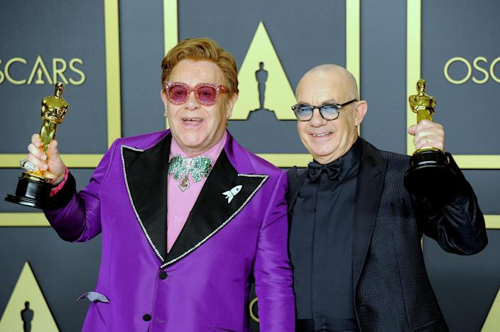 """Sir Elton John and Bernie Taupin pose with their Awards for Best Original Song, """"I'm Gonna Love Me Again"""" ('Rocketman') inside The Press Room of the 92nd Annual Academy Awards held at Hollywood and Highland on February 9, 2020 in Hollywood, California. (Photo by Albert L. Ortega/Getty Images)"""