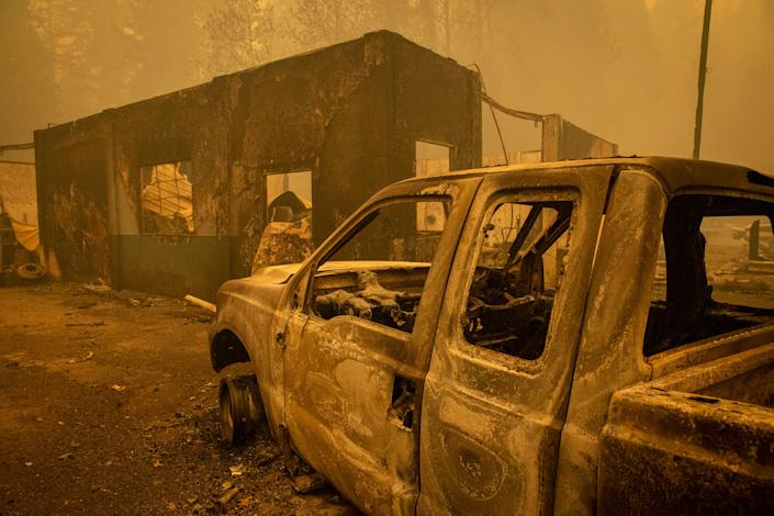 Burned out vehicles destroyed by the Holiday Farm Fire sit outside a shop in Nimrod, Ore. on Sept. 10, 2020.