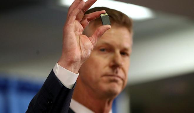 US Attorney David L. Anderson holds an SD memory card during a news conference in September after Xuehua Peng, also known as Edward Peng, was charged with acting as an illegal foreign agent. Photo: Reuters