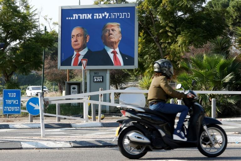 "A billboard depicting Israel's Prime Minister Benjamin Netanyahu (L) and US President Donald Trump side by side with a slogan in Hebrew which reads ""Netanyahu, a different league"", in the Israeli coastal city of Tel Aviv"