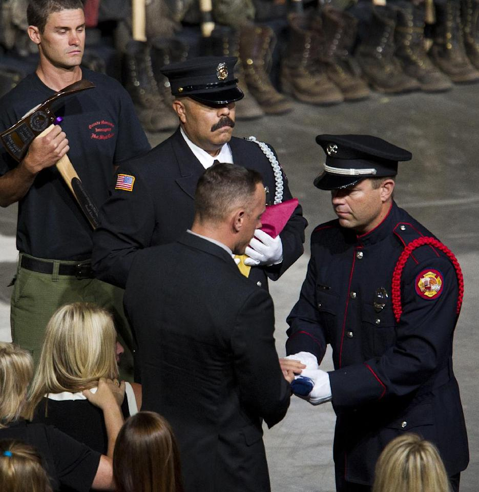 A flag is presented to the family of fallen firefighter Jesse Steed during a memorial service for the 19 fallen firefighters at Tim's Toyota Center in Prescott Valley, Ariz. on Tuesday, July 9, 2013. Prescott's Granite Mountain Hotshots were overrun by smoke and fire while battling a blaze on a ridge in Yarnell, about 80 miles northwest of Phoenix on June 30, 2013. (AP Photo/The Arizona Republic, Michael Chow, Pool)