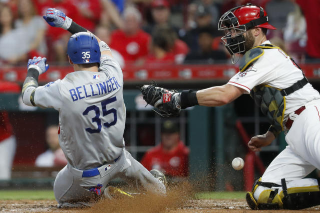 Los Angeles Dodgers' Cody Bellinger (35) scores against Cincinnati Reds catcher Curt Casali, right, on an RBI-single by Enrique Hernandez off relief pitcher Cody Reed in the sixth inning of a baseball game, Friday, May 17, 2019, in Cincinnati. (AP Photo/John Minchillo)