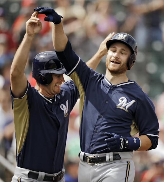 Milwaukee Brewers' Jonathan Lucroy, right, celebrates with Logan Schafer after Lucroy came around to score on a single and three-base error on Cincinnati Reds right fielder Jay Bruce in the second inning of a spring exhibition baseball game Sunday, March 23, 2014, in Goodyear, Ariz. Schafer scored ahead of Lucroy. (AP Photo/Mark Duncan)