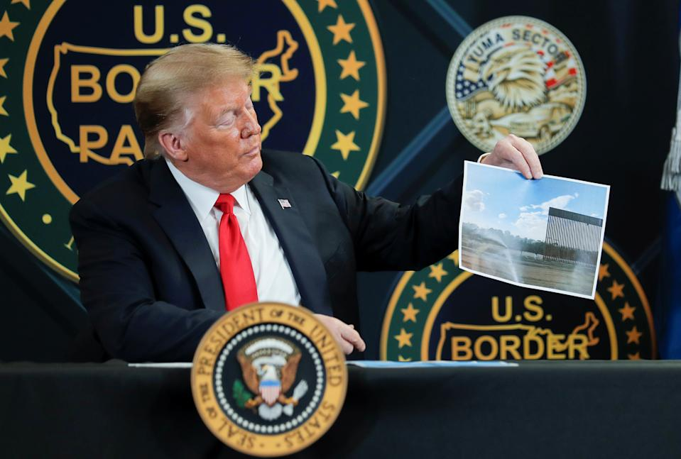 U.S. President Donald Trump holds up a picture of border wall being installed along the U.S.-Mexico border as he participates in a roundtable briefing on border security at the U.S. Border Patrol Yuma Station in Yuma, Arizona, U.S., June 23, 2020. REUTERS/Carlos Barria