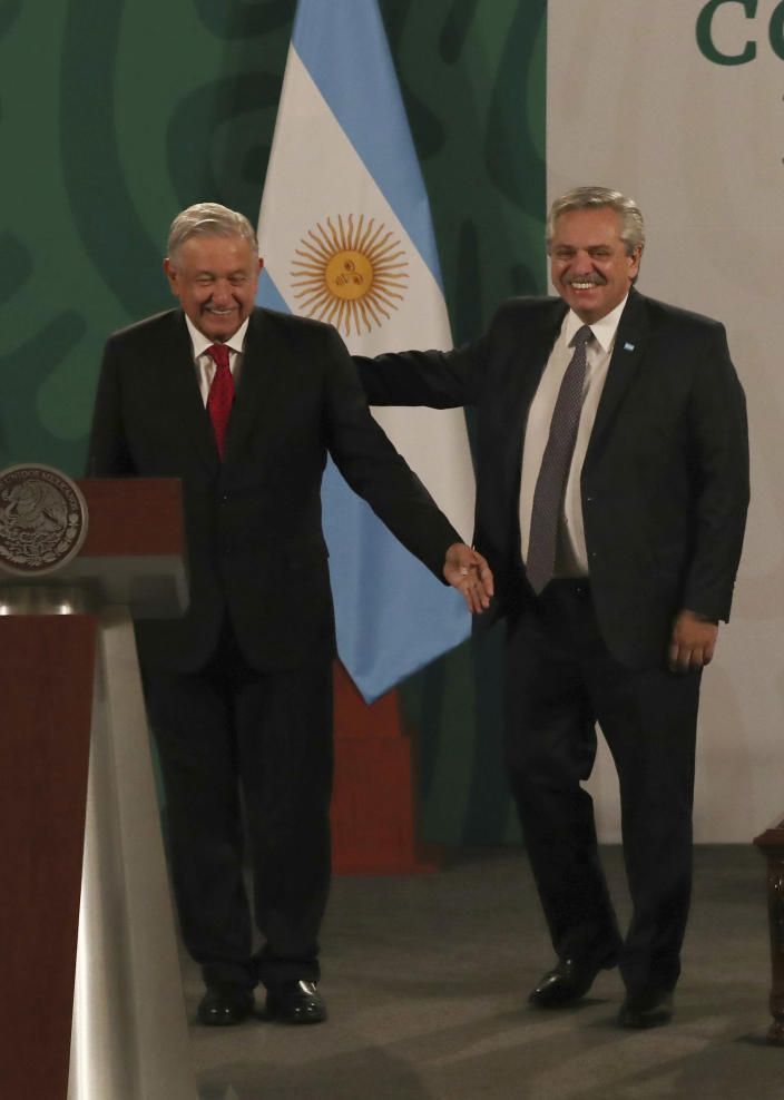 Argentina's President Alberto Fernández, right, arrives with Mexican President Andrés Manuel López Obrador for the Mexican president's daily, morning press conference at the National Palace in Mexico City, Tuesday, Feb. 23, 2021. Fernández is on a four-day official visit to Mexico. (AP Photo/Marco Ugarte)