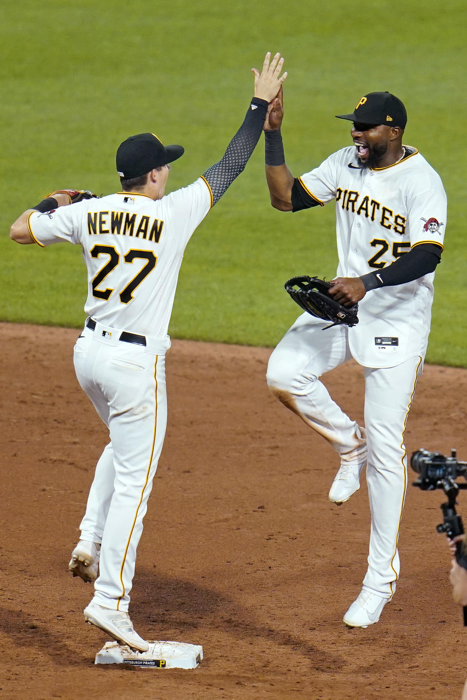 Pittsburgh Pirates' Gregory Polanco (25) and Kevin Newman celebrate after a win over the Cleveland Indians in a baseball game in Pittsburgh, Friday, June 18, 2021. (AP Photo/Gene J. Puskar)