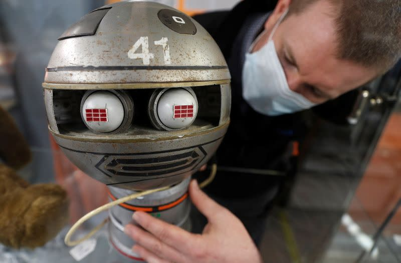 Alastair McCrea of Ewbank's Auctioneers, positions a Zeroid model from Gerry Anderson and Christopher Burr's Terrahawks at their showroom, ahead of a sale in Woking