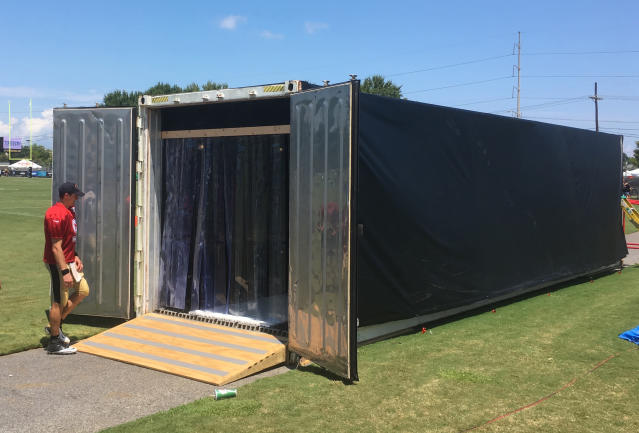 In this Aug. 2, 2018, photo, New Orleans Saints quarterback Drew Brees enters a trailer designed to help players cool down their core body temperatures during training camp practices at New Orleans Saints headquarters in Metairie, La. An 18-wheeler dropped off what looks like a massive storage trailer. Inside, it's actually a chilly 25 degrees featuring dim lighting and black padded folding chairs. (AP Photo/Brett Martel)