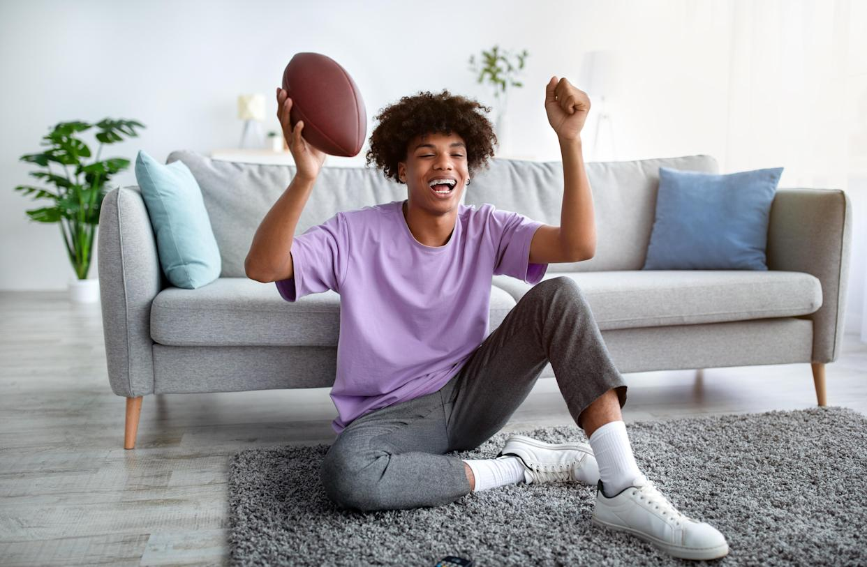 Excited teen holds football while watching TV in living room.