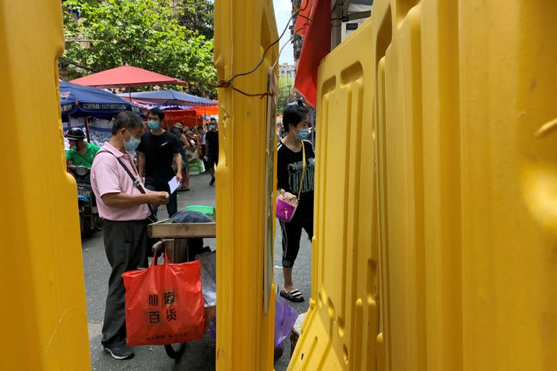 People wearing face masks are seen behind barricades at a market following the coronavirus disease (COVID-19) outbreak in Wuhan