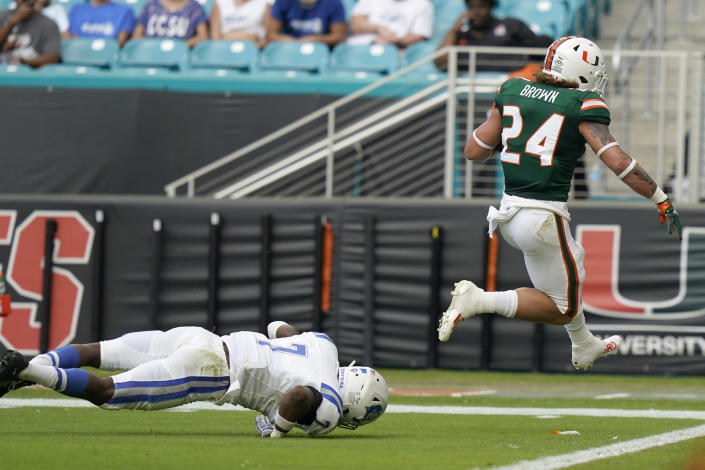 Miami running back Cody Brown (24) scores a touchdown past Central Connecticut State safety Jahlil Brown (7) during the first half of an NCAA college football game, Saturday, Sept. 25, 2021, in Miami Gardens, Fla. (AP Photo/Lynne Sladky)