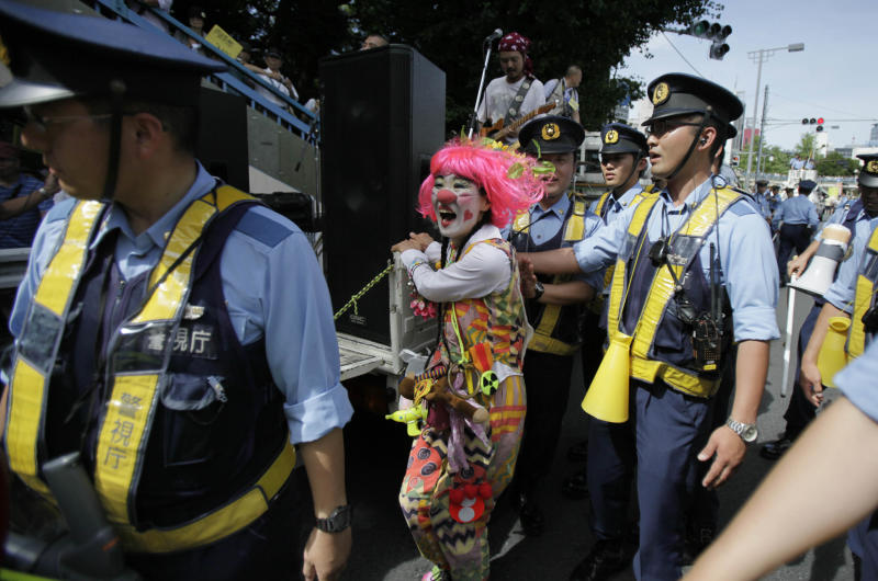 """An anti-nuclear protester dressed as a clown is moved on by police during a march through downtown Tokyo, Monday, July 16, 2012. Tens of thousands of people gathered at a Tokyo park, demanding """"Sayonara,"""" or goodbye, to nuclear power as Japan prepares to restart yet another reactor, and expressed outrage over a report that blamed culture on the Fukushima disaster. (AP Photo/Greg Baker)"""