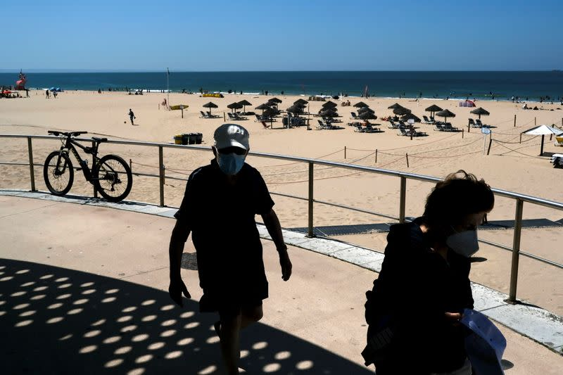 People walk at Carcavelos beach amid COVID-19 pandemic, in Cascais