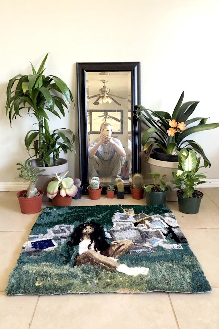 """Oscar Morales, reflected in a mirror, with the rug he made based on SZA's """"Ctrl"""" album cover."""