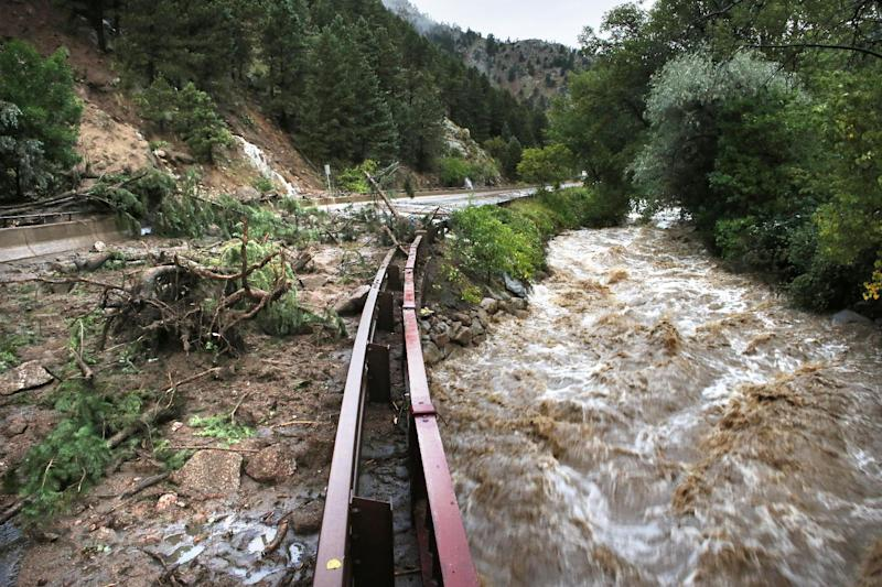 Boulder Creek flows at high speed next to a road closed off by debris from flooding at the base of Boulder Canyon, Colo., Friday, Sept. 13, 2013. People in Boulder were ordered to evacuate as water rose to dangerous levels amid a storm system that has been dropping rain for a week. (AP Photo/Brennan Linsley)