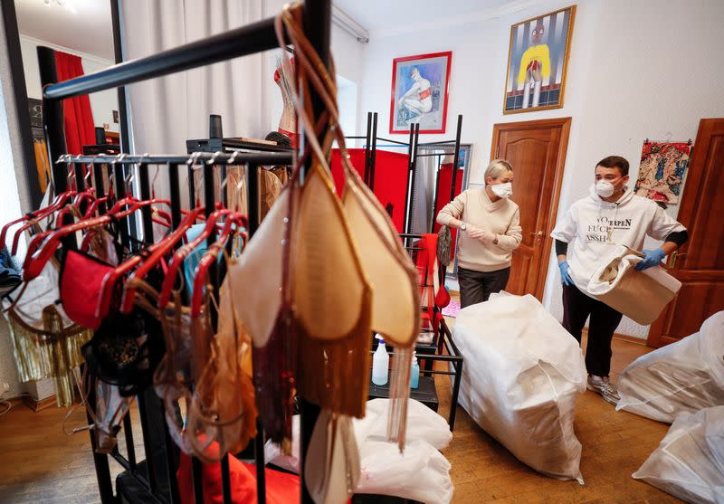 Ukrainian fashion designer Frolov holds patterns for medical protective coveralls in his show room in Kiev