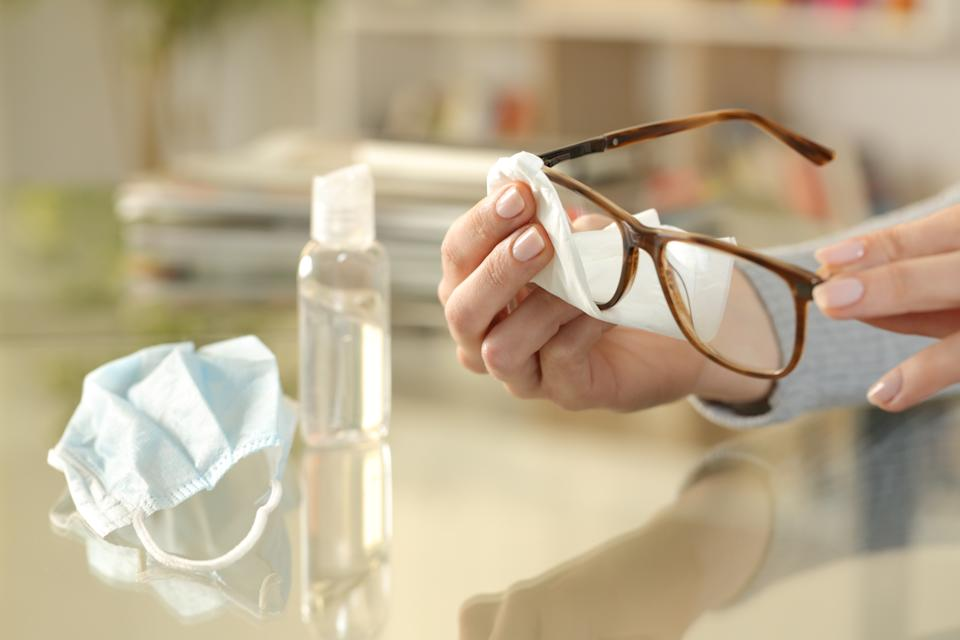 Close up of woman hand with protective mask cleaning eye glasses with sanitizer and cloth sitting on a desk at home