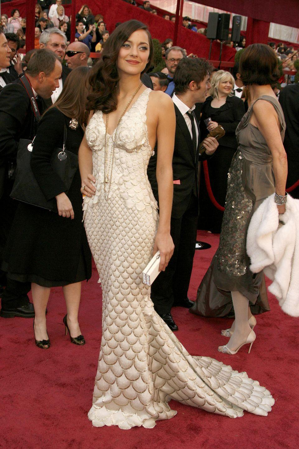 <p>Marion wore a mermaid dress to the red carpet in the most literal sense. She looked radiant in this Jean Paul Gaultier gown that featured a golden scale-like pattern. She grew to international fame that year after her breakout role as Édith Piaf in <em>La Vie en Rose</em>, which earned her the Best Actress award.</p>