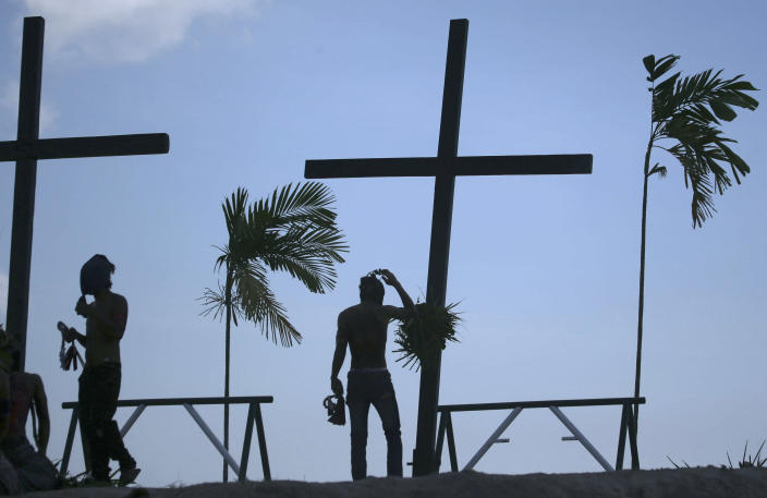 Filipino penitents stop before wooden crosses during Good Friday rituals on March 29, 2013 at Cutud, Pampanga province, northern Philippines. Several Filipino devotees had themselves nailed to crosses Friday to remember Jesus Christ's suffering and death, an annual rite rejected by church leaders in this predominantly Roman Catholic country. (AP Photo/Aaron Favila)