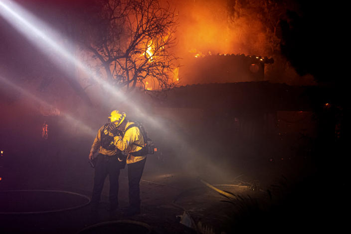 Firefighters recoil from smoke and heat from a fully engulfed house on Jolette Way in Granada Hills North, Calif., early Friday morning, Oct. 11, 2019. (David Crane/The Orange County Register via AP)